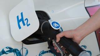 """Der Tankdeckel Autos mit der Aufschrift """"H2"""" für Wasserstoff steht offen und der Tank wird an einer Zapfsäule befüllt. (Foto: dpa Bildfunk, picture alliance / Sebastian Kahnert / dpa-Zentralbild / dpa)"""