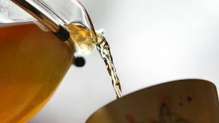 Tee wird aus einer Teekanne in eine Tasse gegossen (Foto: dpa Bildfunk, picture alliance/Karl-Josef Hildenbrand/dpa)