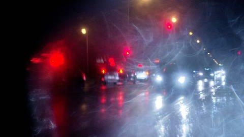 Durch eine Frontscheibe ist bei Regen eine unübersichtliche Verkehrssituation im Dunkeln zu sehen. (Foto: dpa Bildfunk, picture alliance / dpa)