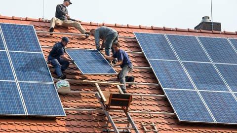 Installateure befestigen Solar-Panele für eine neue Photovoltaik-Anlage auf dem Dach eines Wohn-Hauses. (Foto: dpa Bildfunk, picture alliance / dpa | Patrick Pleul)