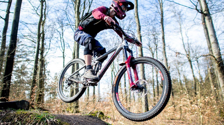 Ein junger Mann springt mit seinem Mountainbike über eine Anhöhe auf einer Downhillstrecke im Deister