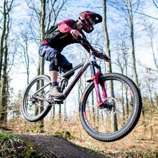 Ein junger Mann springt mit seinem Mountainbike über eine Anhöhe auf einer Downhillstrecke im Deister (Foto: dpa Bildfunk, picture alliance/dpa | Hauke-Christian Dittrich)