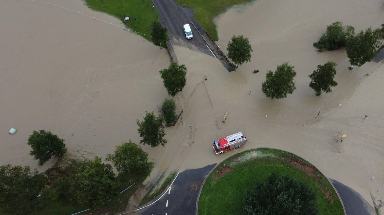Luftaufnahme von einem Feuerwehrfahrzeug, das durch das hoch stehende Wasser an einem Kreisverkehr fährt.