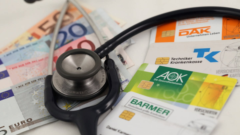 Geld, Krankenkassenkarten und ein Stethoskop (Foto: dpa Bildfunk, dpa / Daniel Karmann)
