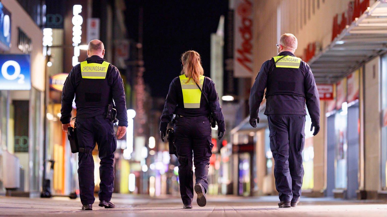Das Ordnungsamt kontrolliert die nächtliche Ausgangssperre in einer Großstadt. (Foto: dpa Bildfunk, picture alliance / Geisler-Fotopress | Christoph Hardt/Geisler-Fotopres)