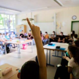 Ein Schüler meldet sich in einer Klasse. Für die letzten fünf Wochen vor den Sommerferien gibt es in Rheinland-Pfalz noch einmal Präsenzunterricht mit allen Schülerinnen und Schülern.  (Foto: dpa Bildfunk, picture alliance/dpa   Christoph Soeder)