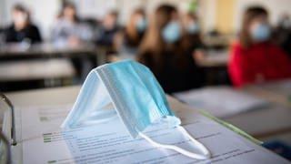 Maske liegt auf einem Tisch in einem Klassenraum (Foto: dpa Bildfunk, picture alliance/dpa | Matthias Balk)