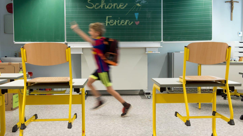Ein Schüler stürmt freudig aus dem Klassenzimmer in die Ferien. Manche Schüler in Rheinland-Pflaz drücken allerdings in den Sommerferien in der Sommerschule die Schulbank.