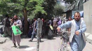 Mann mit Fahrrad und andere Männer im Hintergrund auf einer Straße (Foto: SWR)