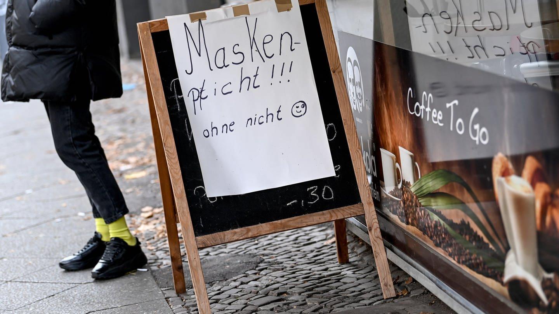 Vor einem Laden weist ein Schild mit der Aufschrift