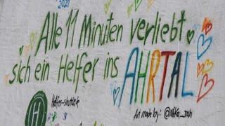 """""""Alle 11 Minuten verliebt sich ein Helfer ins Ahrtal"""" steht auf einer Hausfassade in der von der Flutkastastrophe getroffenen Ahrgemeinde Dernau. (Foto: dpa Bildfunk, Picture Alliance)"""