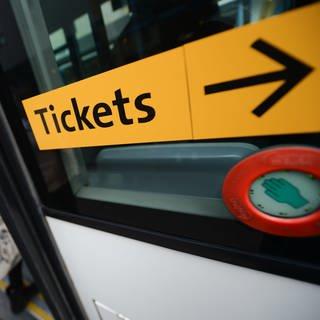 """Ein Aufkleber mit der Aufschrift """"Tickets"""" ist an einem Bus angebracht. Die Landesregierung von Rheinland-Pfalz plant, den öffentlichen Nahverkehr von einer freiwilligen zu einer verpflichtenden Aufgabe für die Kommunen zu machen. (Foto: dpa Bildfunk, picture alliance/Arne Dedert/dpa)"""