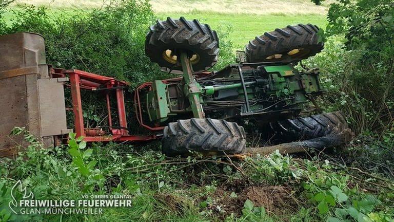 Ein Traktor liegt auf dem Kopf am Fuß einer Böschung