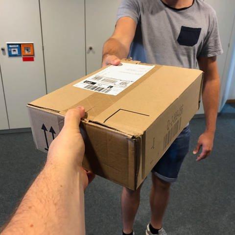 Ein ausgesteckter Arm überreicht einem anderen ausgestreckten Arm ein Paket. (Foto: SWR)