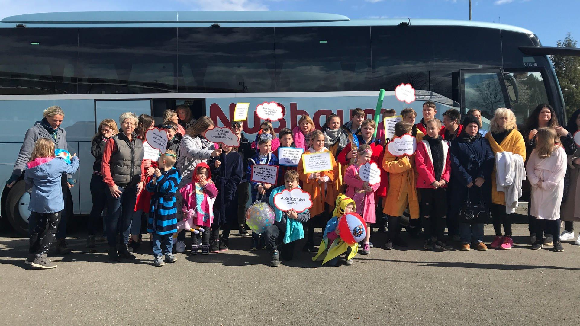 Eine Gruppe Menschen steht vor einem Reisebus. Die Erwachsenen und Kinder tragen Bademäntel und halte selbst gebastelte Protestschilder in den Händen.