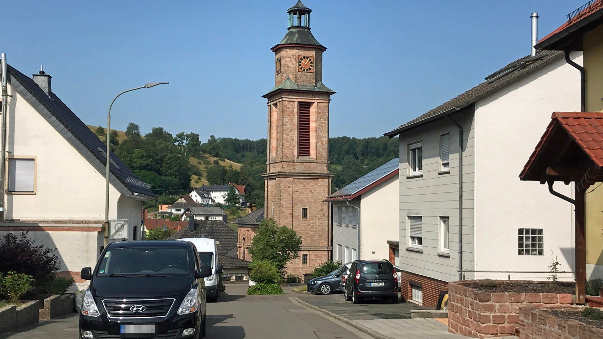 Sandsteinkirche mit Glockenturm am Ende einer Dorfstraße