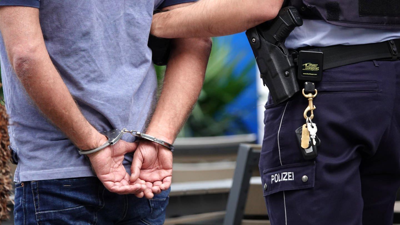 Ein Mann wird von einem Polizisten abgeführt (Foto: dpa Bildfunk, Picture Alliance/Johannes Neudecker)