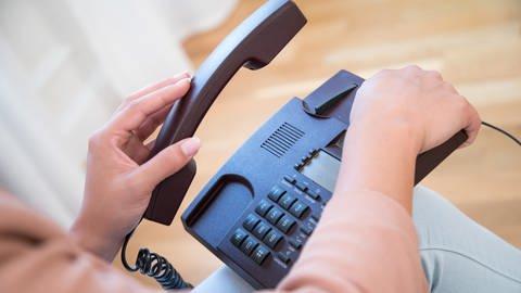 """Eine Frau legt einen Telefonhörer auf - Die Polizei Koblenz warnt vor Betrügern, die sich derzeit als Mitarbeiter des Mobilfunkanbieters """"Vodafone"""" ausgeben.  (Foto: SWR)"""