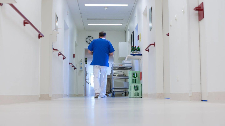 Ein Krankenpfleger geht über einen Flur in einem Krankenhaus. (Foto: dpa Bildfunk, picture alliance / Philipp Schulze/dpa)