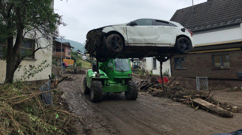 Ein kleiner Traktor fährt ein kaputtes Auto weg in Schuld nach dem Hochwasser der Ahr