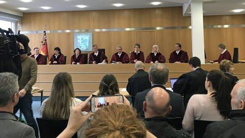 Die Richter am Verfassungsgerichtshof Rheinland-Pfalz in Koblenz in roten Roben stehen am Richterpult und eröffnen die Verhandlung (Foto: SWR)