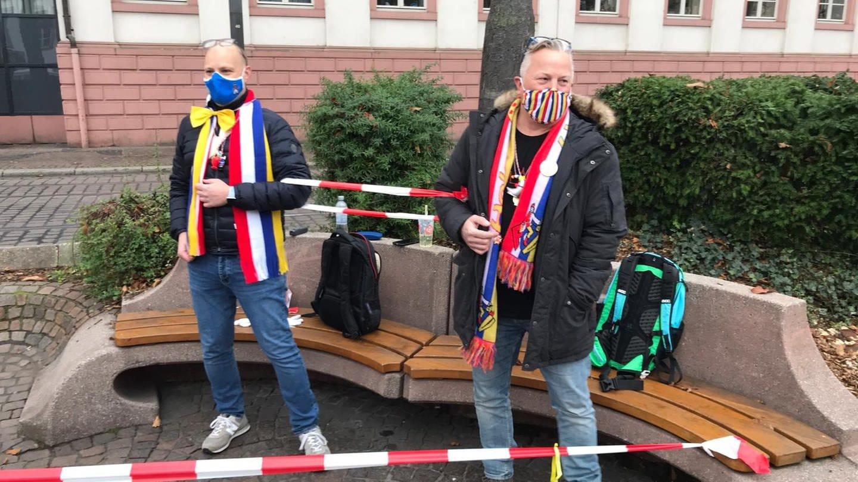 Zwei Männer haben sich am Schillerplatz eine Bank mit Flatterband abgesperrt und feiern bunt kostümiert - mit Maske und Abstand