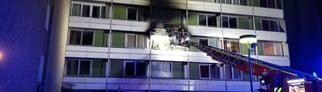 Eine lange Drehleiter der Feuerwehr steht vor dem verrauchten Balkon im zweiten Stock des Mainzer Hochhauses. (Foto: mainz112)