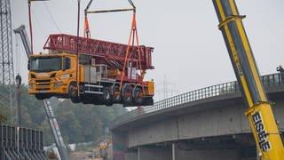 Ein Schwerlastkran hebt ein Spezialfahrzeug von der maroden Salzbachtalbrücke in Wiesbaden. (Foto: dpa Bildfunk, Picture Alliance)