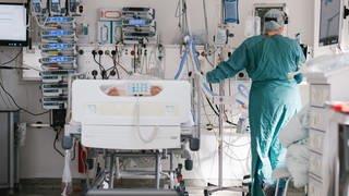 Eine Intensivpflegerin versorgt auf einer Intensivstation einen an Covid-19 erkrankten Patienten.  (Foto: dpa Bildfunk, Ole Spata)