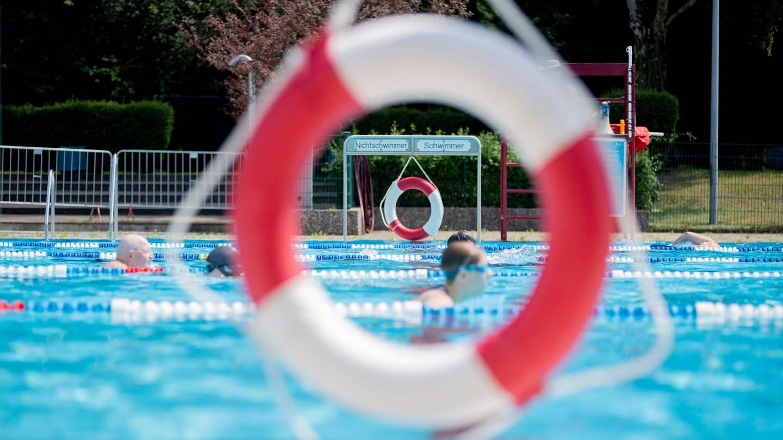 Blick auf ein Freibad durch einen Schwimmring
