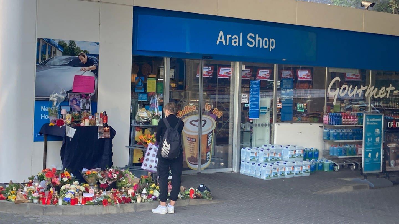 Menschen legen Blumen und Kerzen vor der Tankstelle in Idar-Oberstein ab, wo der 20-jährige Kassierer erschossen wurde.