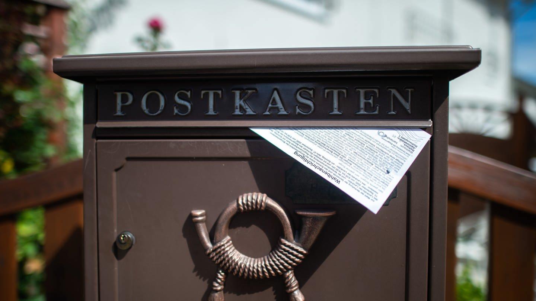 Eine Wahlbenachrichtigung liegt in einen Briefkasten. Ab heute werden in Nordrhein-Westfalen die Wahlbenachrichtigungen für die Kommunalwahlen, die Landratswahlen, die Bürgermeisterwahlen und die Verbandsversammlungswahlen am 13. September zugestellt. (Foto: Imago, dpa Bildfunk, 221328369)