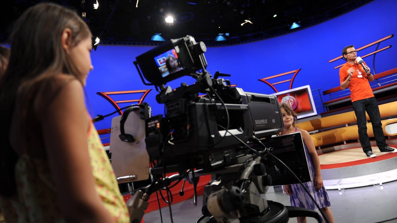 Ein Mädchen steht im Flutlicht-Fernsehstudio vor einer Kamera (Foto: SWR, Ben Pakalski)