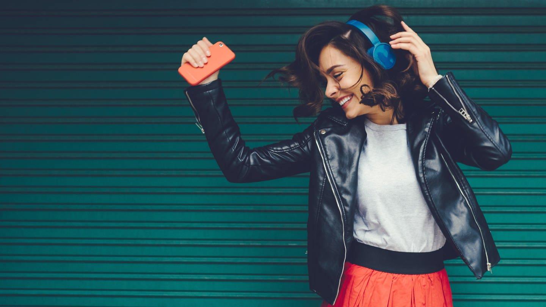 Junge Frau hört Musik und tanzt