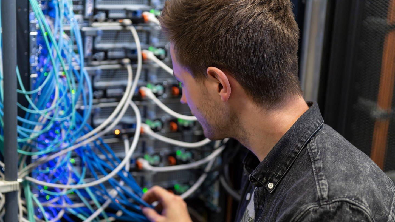 Ein junger Mann repariert etwas im Serverraum (Foto: SWR, Alexander Kluge)