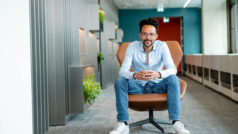 Mann in sitzender Position mit Kaffeebecher