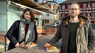 Katharina Röben und Tobias Koch stehen an einem Stehtisch vor einem Imbis, auf dem Tisch ein Burger und eine Currywurst. (Foto: SWR, solisTV)
