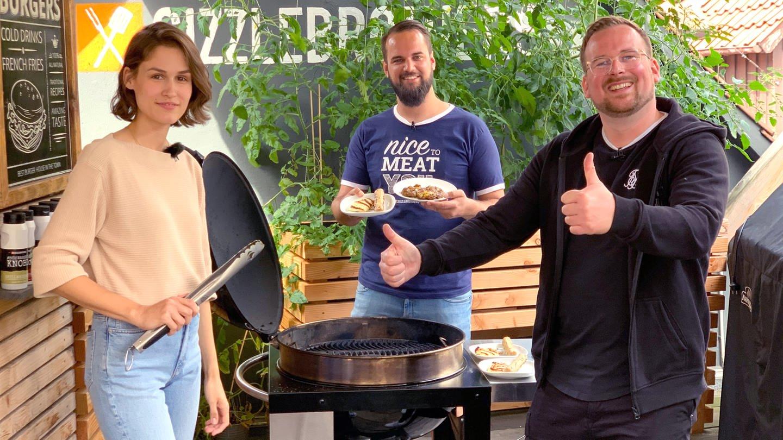 Katharina Röben hält eine Grillzange in der Hand. Neben ihr stehen ein Kugelgrill und die zwei Youtuber von Sizzle Brothers. (Foto: SWR, solisTV)