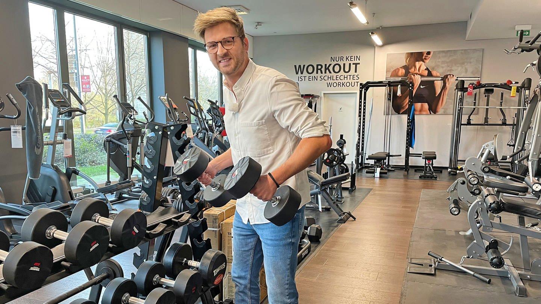 SWR Moderator Johannes Zenglein steht in einem Fitnessstudio vor vielen Hanteln und hält in beiden Händen je eine Hantel. Er hebt sie hoch und guckt dabei angestrengt.