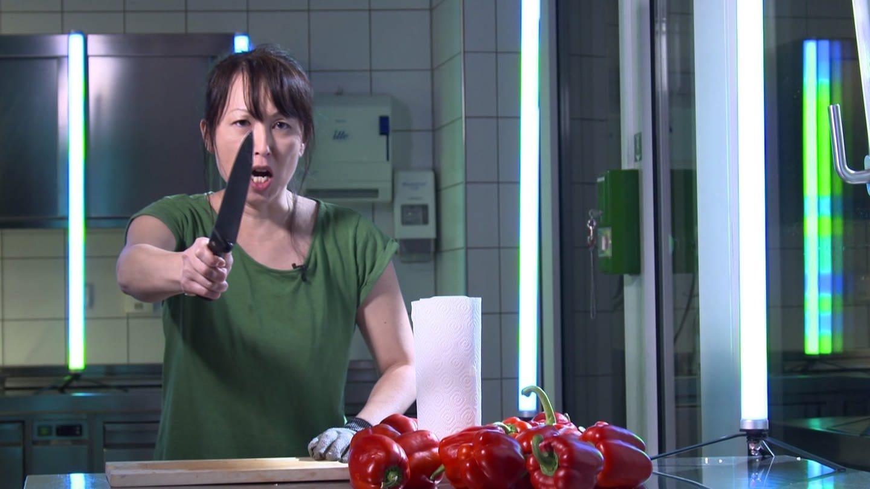 Wakako Nakaso steht in der Küche und streckt die Hand mit einem Messer über dem Paprika aus
