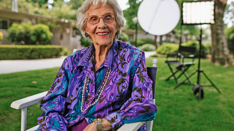 Connie Sawyer in in blau-lila Kleid sitzt in einem Stuhl und lächelt in die Kamera.
