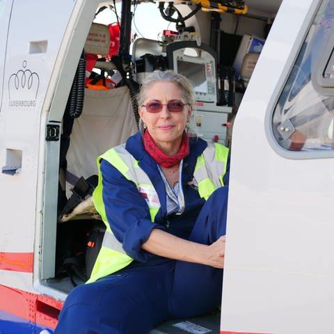 """Dr. Annemay Huppert sitzt in Seitentür des Rettungshubschraubers """"Air Rescue 3"""". (Foto: SWR)"""