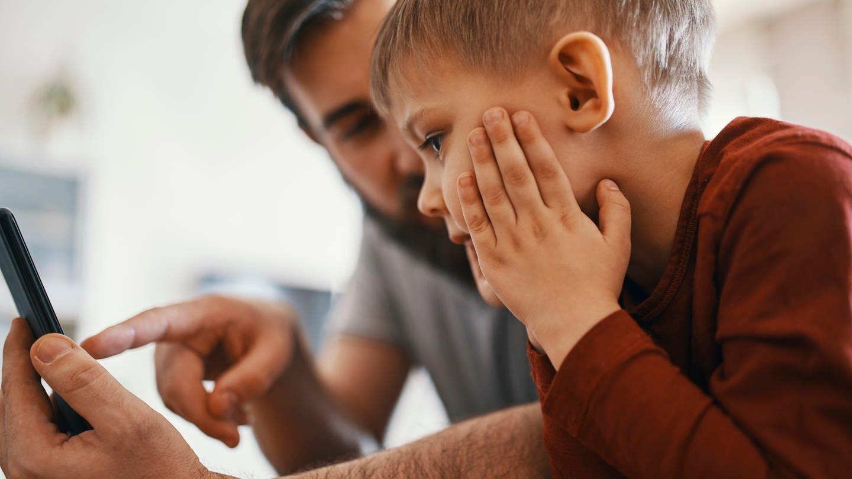 Vater und Sohn mit einem Smartphone (Foto: Getty)