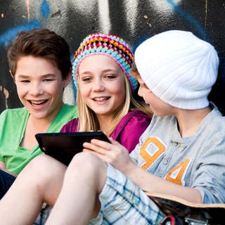 Drei Teenager mit Tablet (Foto: Thinkstock)