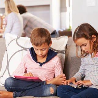 Ein Junge und ein Mädchen mit Smartphone und Tablet auf dem Sofa, im Hintergrund Erwachsene (Foto: Getty Images)