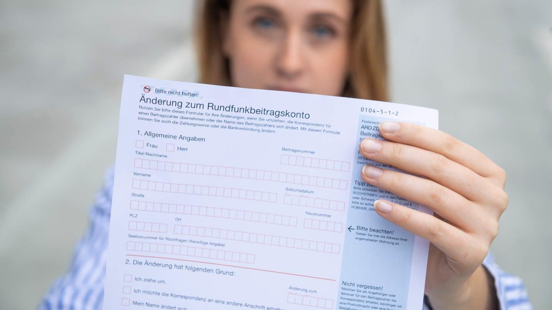 Das bild zeigt eine Frau, die ein Formular zum Rundfunkbeitrag in der Hand hält (Foto: SWR)