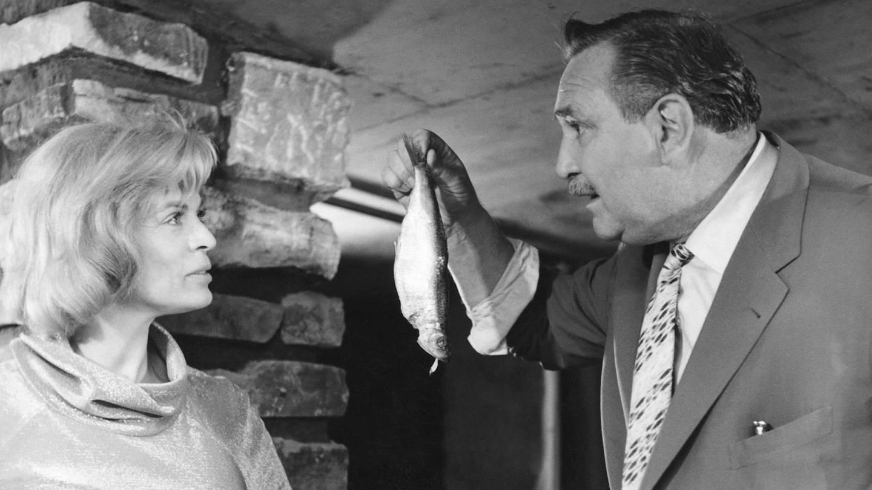 Gustav Knuth hält einen Fisch in der Hand und redet mit Renate Schacht.