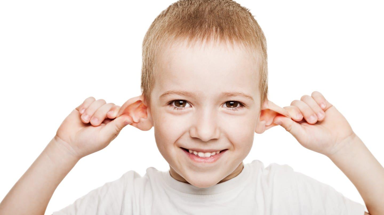 Junge zieht sich an beiden Ohren und lacht: Er hat es wohl faustdick hinter den Ohren (Foto: Colourbox)