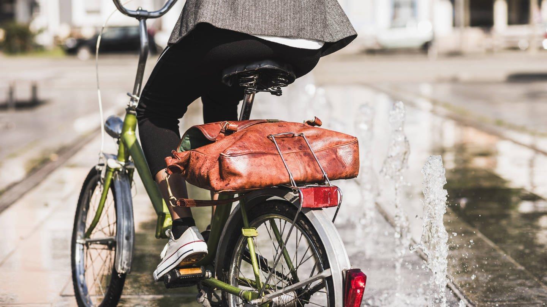 Radfahrerin mit Aktentasche auf dem Gepäckträger: Durch Radfahren kann man seine persönliche Klimabilanz verbessern (Foto: Imago, imago images / Westend61)