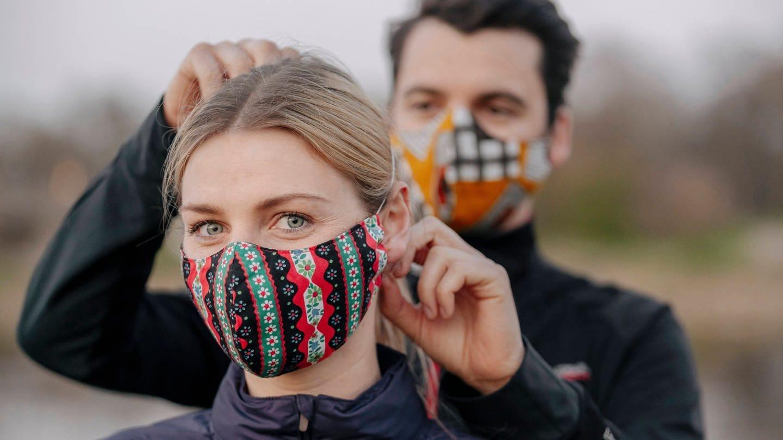 Ein Mann und eine Frau mit Mund-Nase-Schutz. Ob Frauen seltener an Covid-19 erkranken oder leichtere Verläufe haben, ist noch nicht ausreichend erforscht (Foto: Imago, imago images / Westend61)